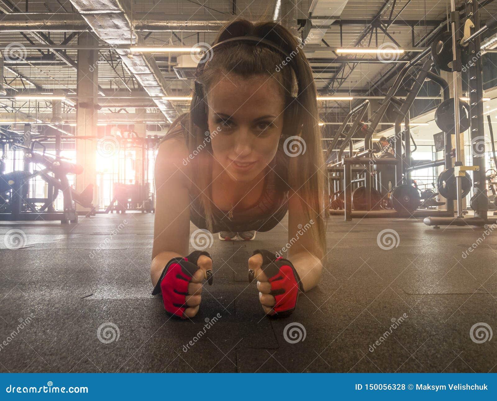 M?sica de escuta da mulher da aptid?o em fones de ouvido sem fio Fazendo exercícios do exercício no gym Menina apta atlética boni