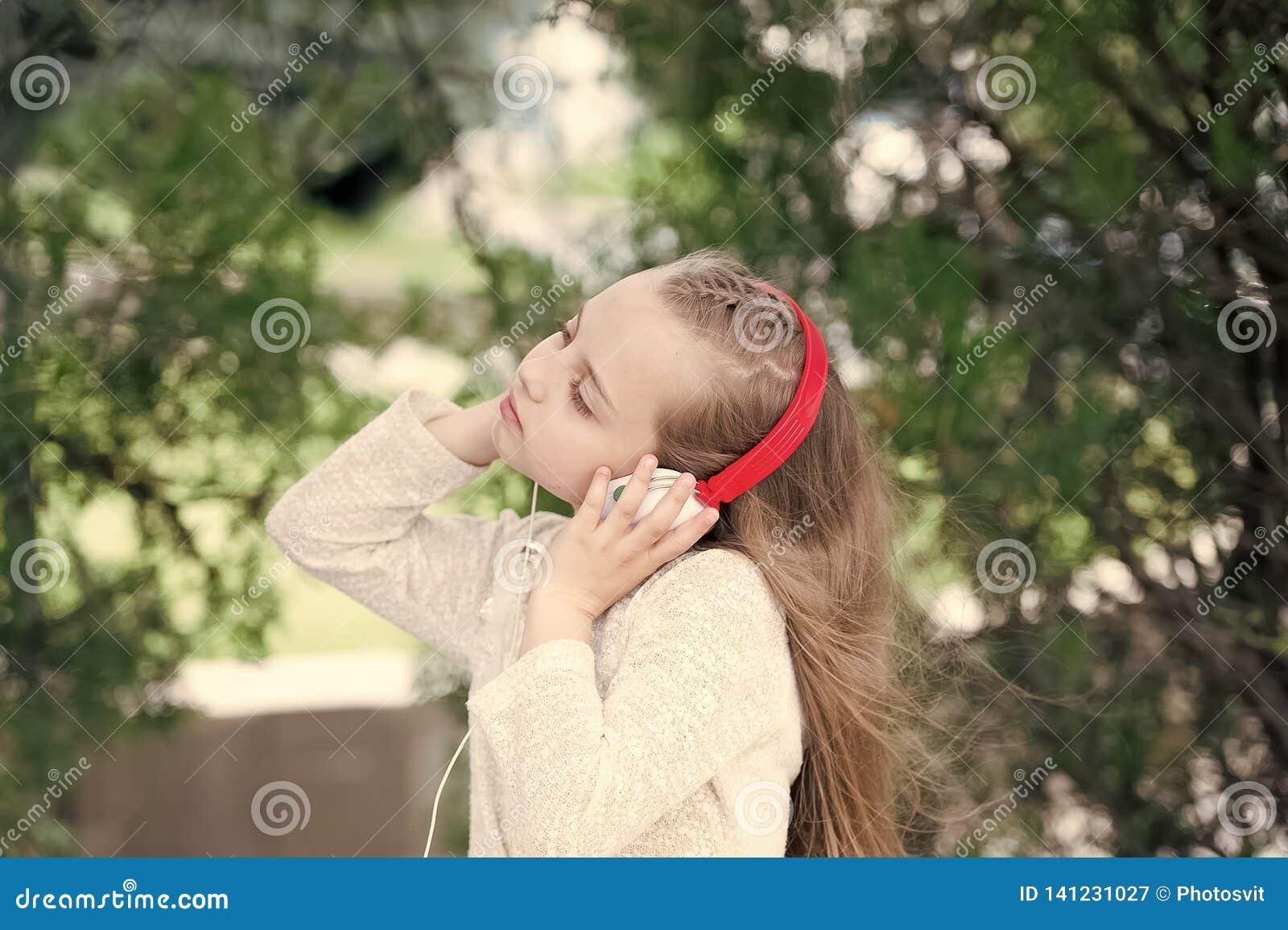 Mała dziewczynka słucha muzykę w lato parku Melodia dźwięk i mp3 Dziecko cieszy się muzykę w hełmofonach plenerowych Moda dziecia