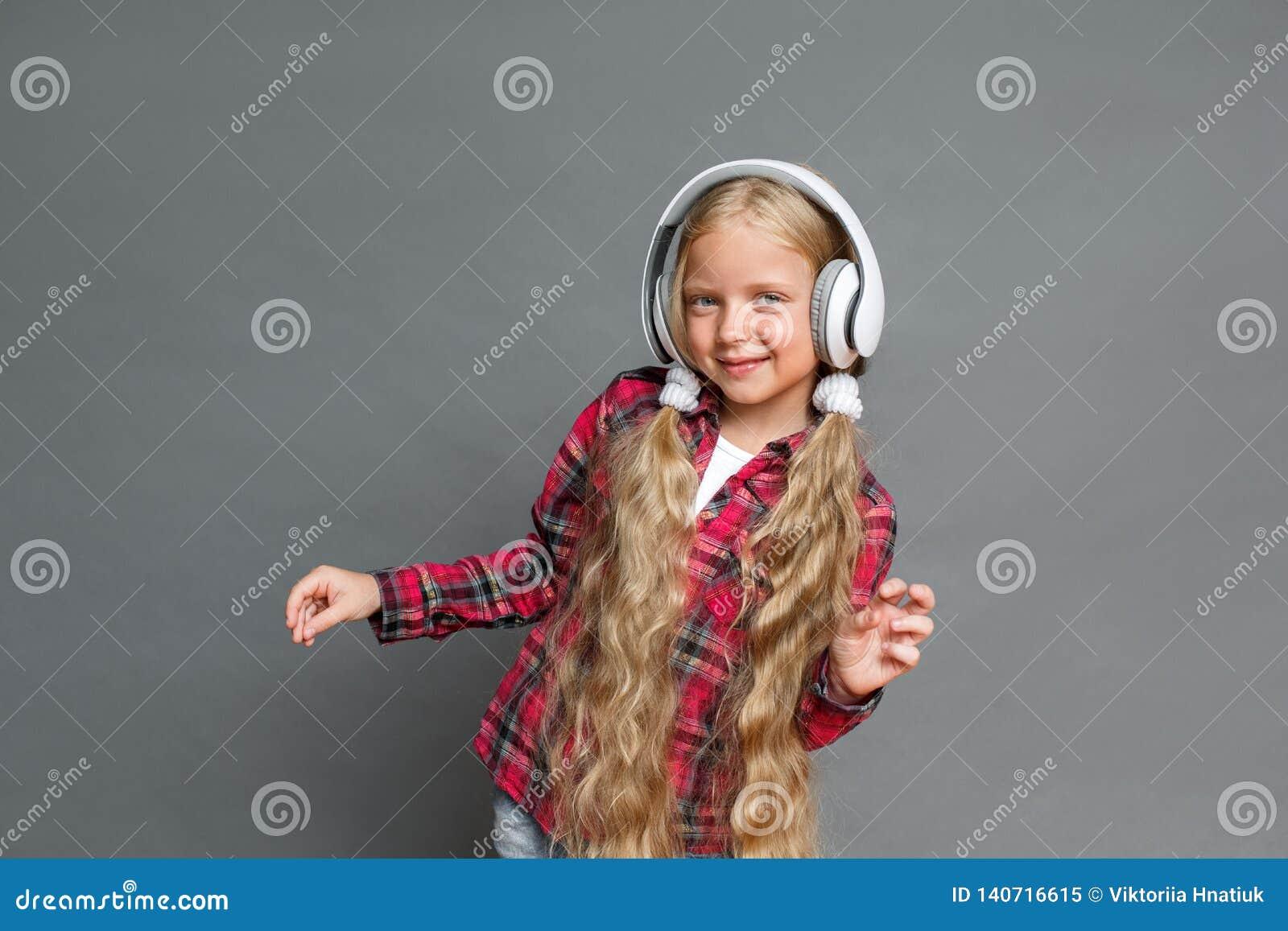 Mała dziewczynka w hełmofonach z ponytails stać odizolowywam na popielaty słuchający muzyczny dancingowy radosnym
