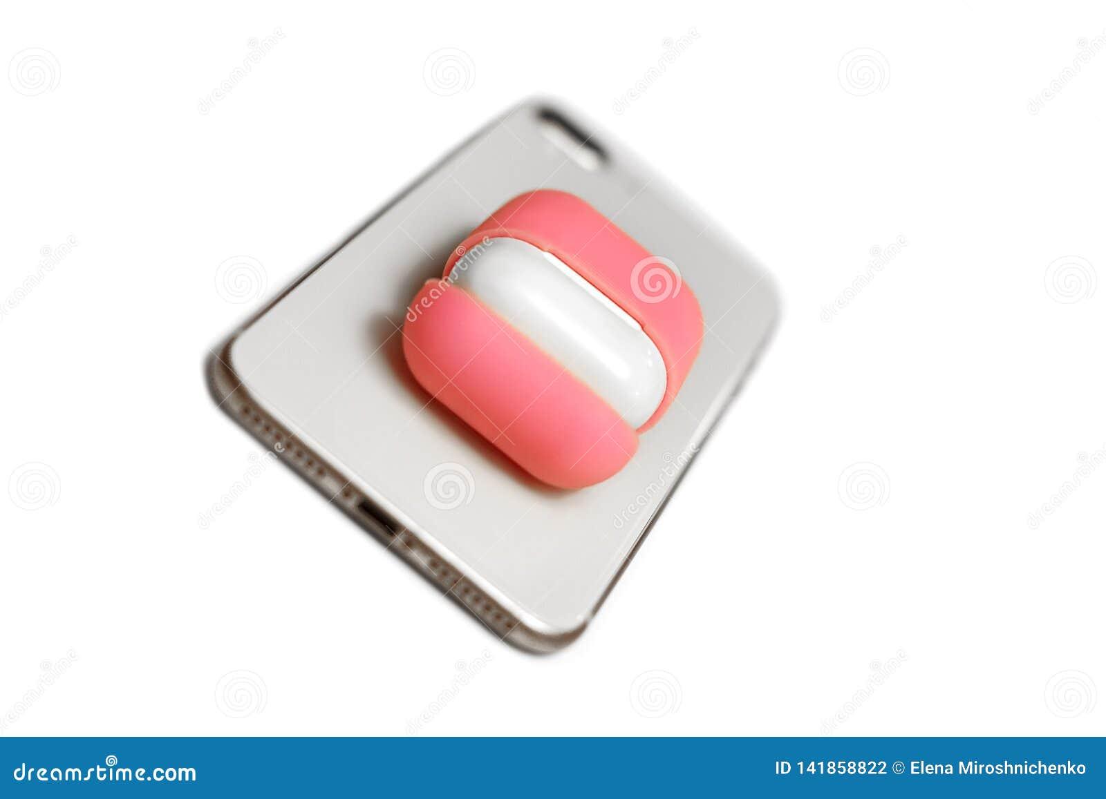 Małe białe słuchawki z ładowarki pudełkiem w jaskrawym menchii pokrywy pudełku, telefon komórkowy, wybierająca ostrość, dinamic w