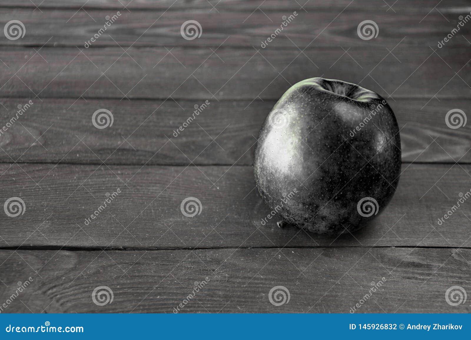A ma?? preta encontra-se em uma tabela de madeira cinzenta contra