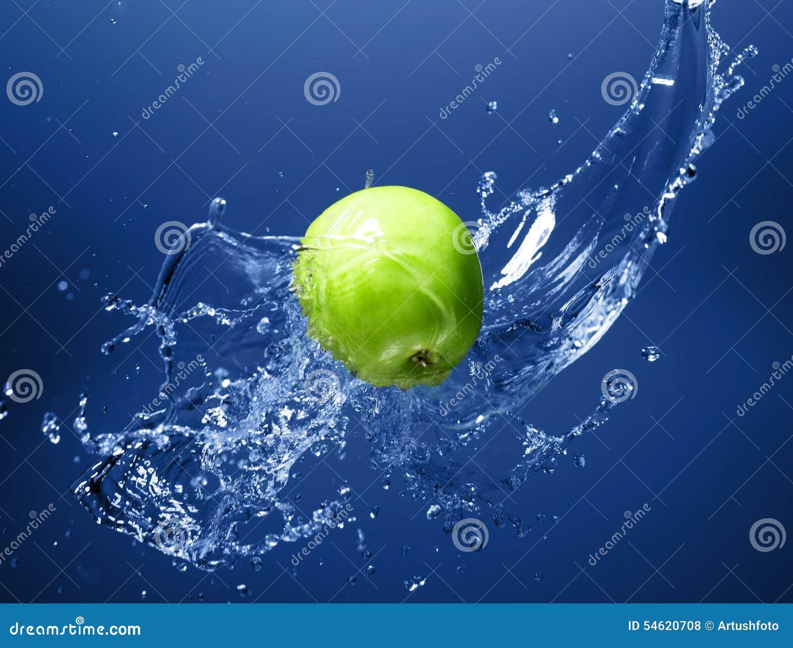 Maçã verde com respingo da água, na água azul