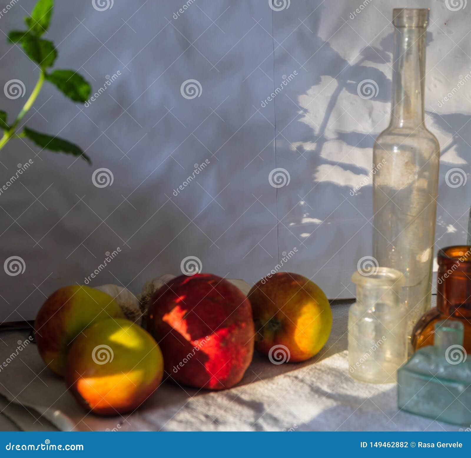 Ma??s amarelas vermelhas borradas, rom? vermelha, folha da hortel? e garrafas do vintage na luz solar com sombras Fim acima