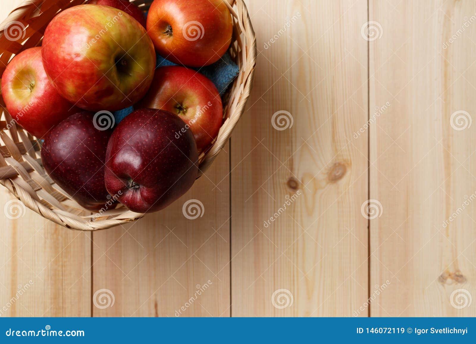 Maçãs vermelhas maduras em uma cesta em um de madeira brilhante