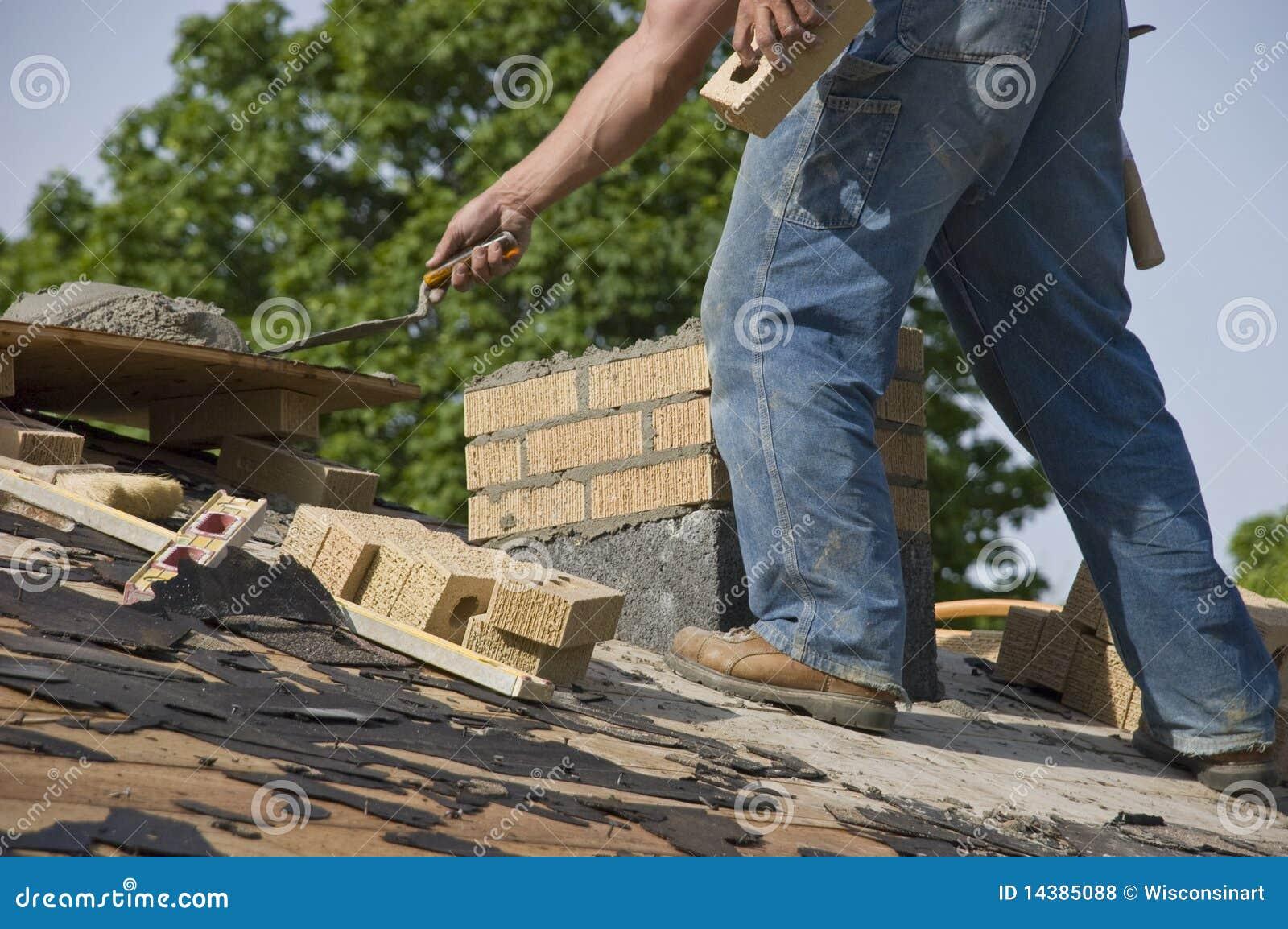Maçon de maçon étendant des briques de cheminée sur la Chambre