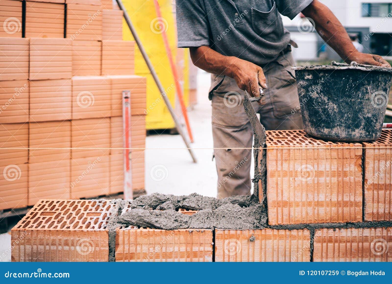 Maçonnerie, maçon industriel de brique, maçon travaillant à construire les murs extérieurs au chantier de construction