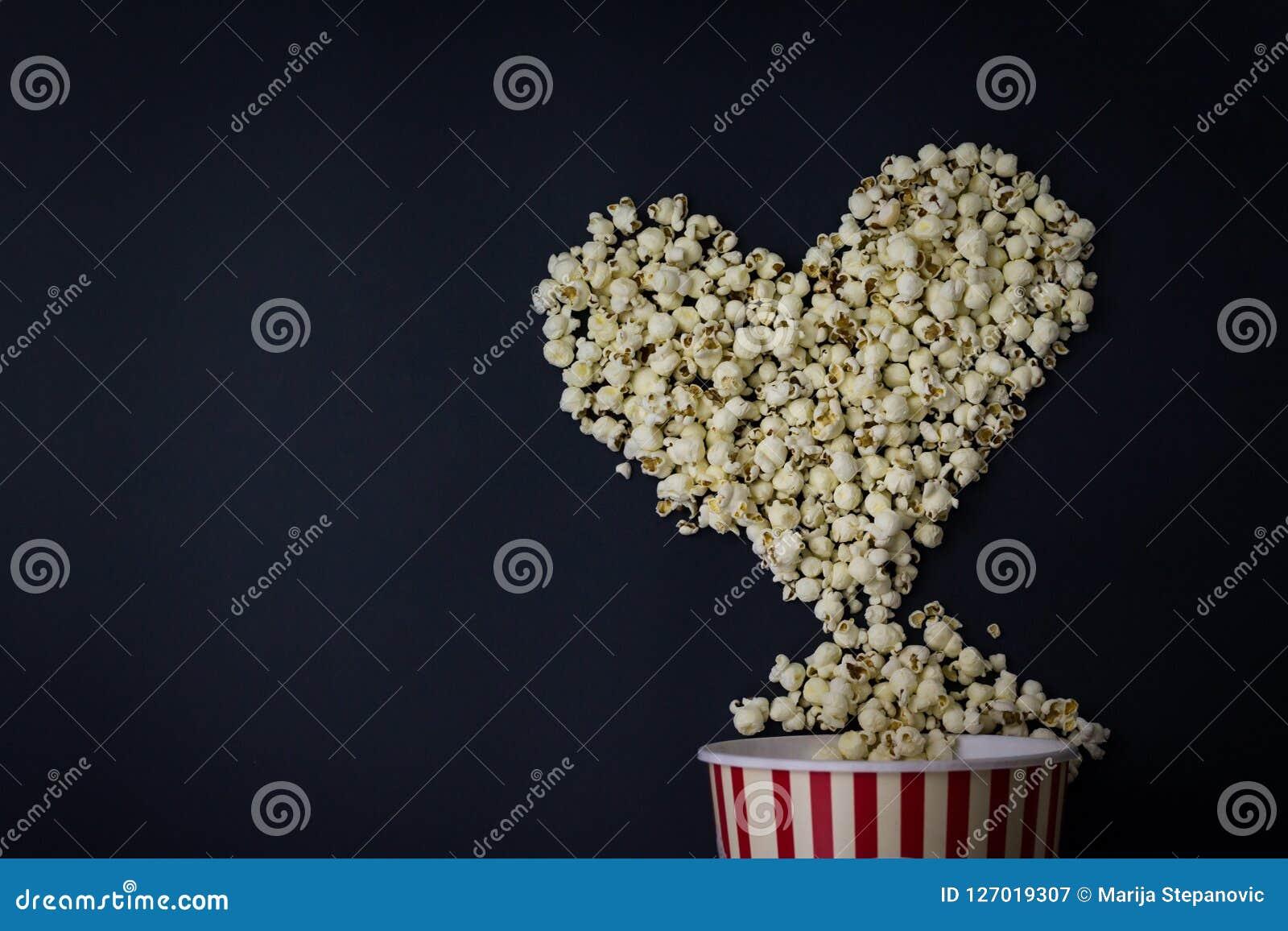 Maïs éclaté dans la forme de coeur sur le fond noir Amant de film