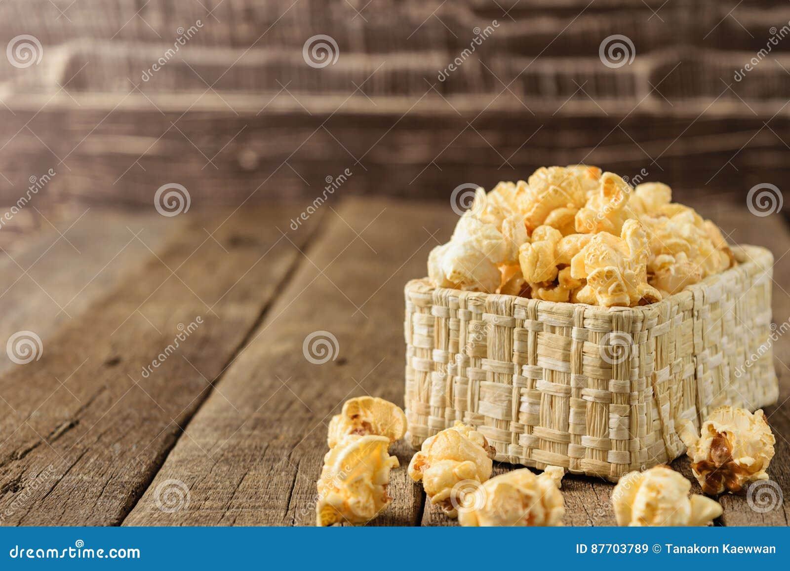 Maïs éclaté dans les paniers en osier sur le woodbackground de table