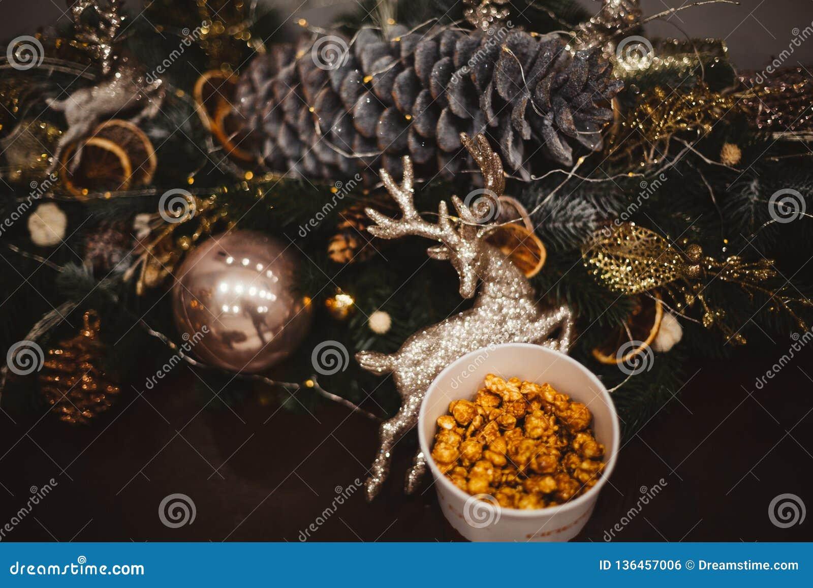Maïs éclaté dans un plat en bois sur le fond des arbres de Noël et des décorations de Noël, offre de nouvelle année, foyer sélect