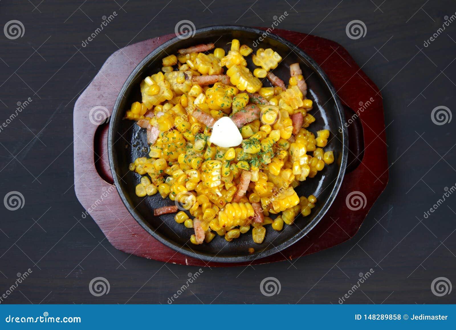 Maïs beurré avec le lard sur une table de salle à manger
