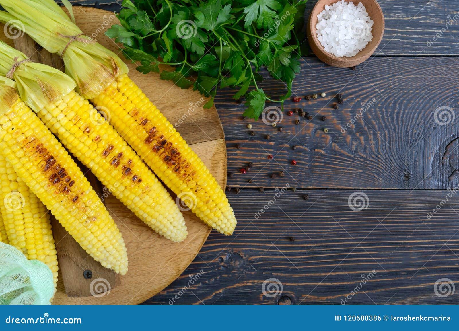 Maïs grillé savoureux frais avec du beurre, le sel de mer et le cilantro sur une table en bois