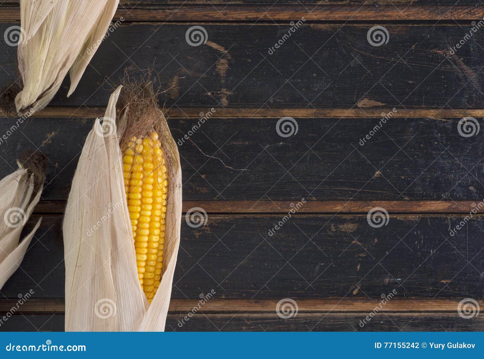 Maïs jaune mûr sur une vieille table en bois foncée