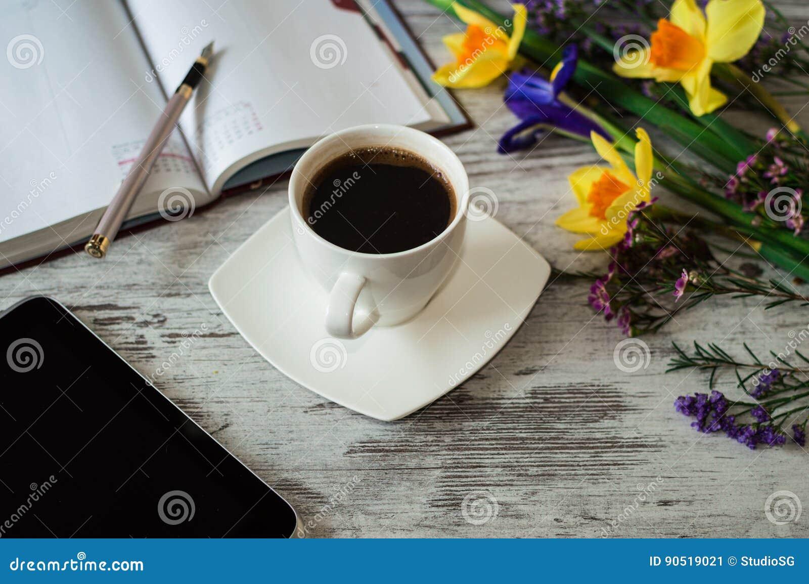 Mañana aromática del trabajo con la taza de café sólo