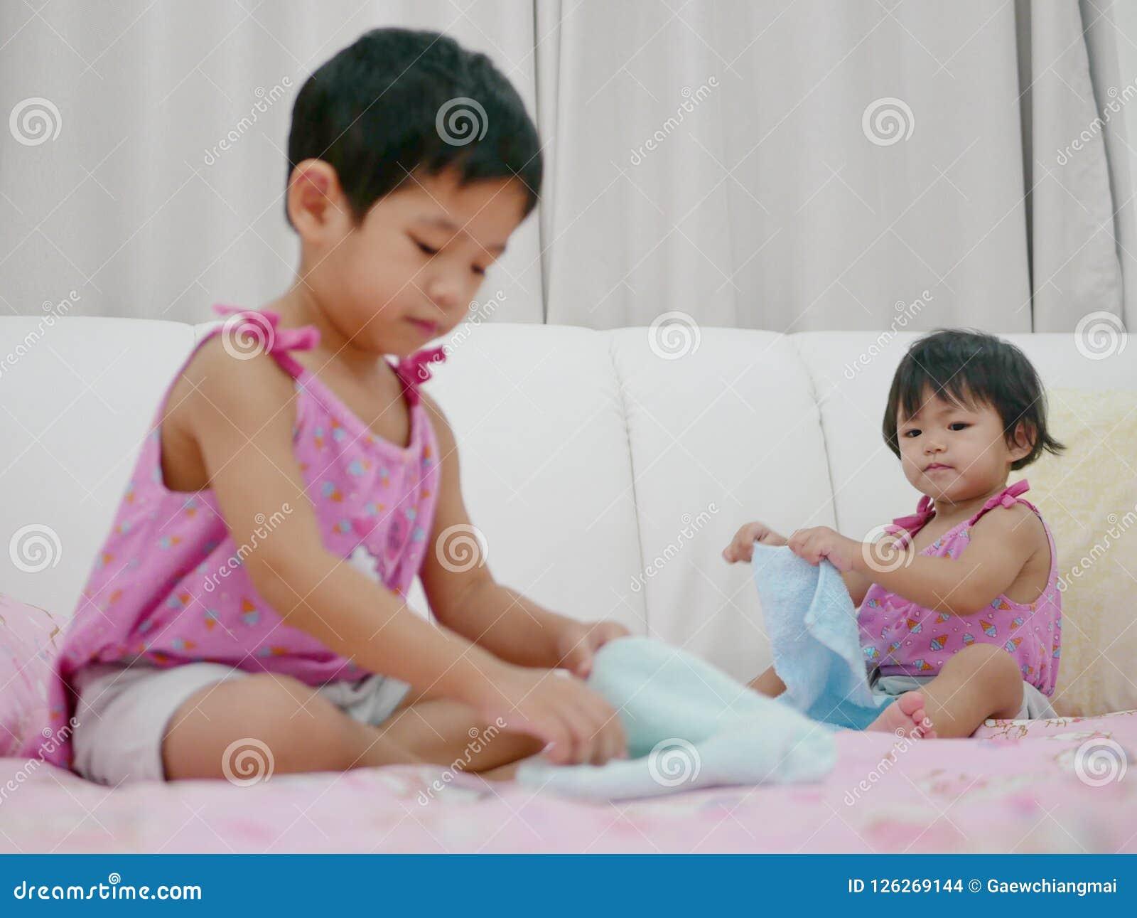 Mała Azjatycka dziewczynka, 18 miesięcy starzy, jej stara siostrzana falcowanie próba, ubrania, i robić ten sam rzeczy