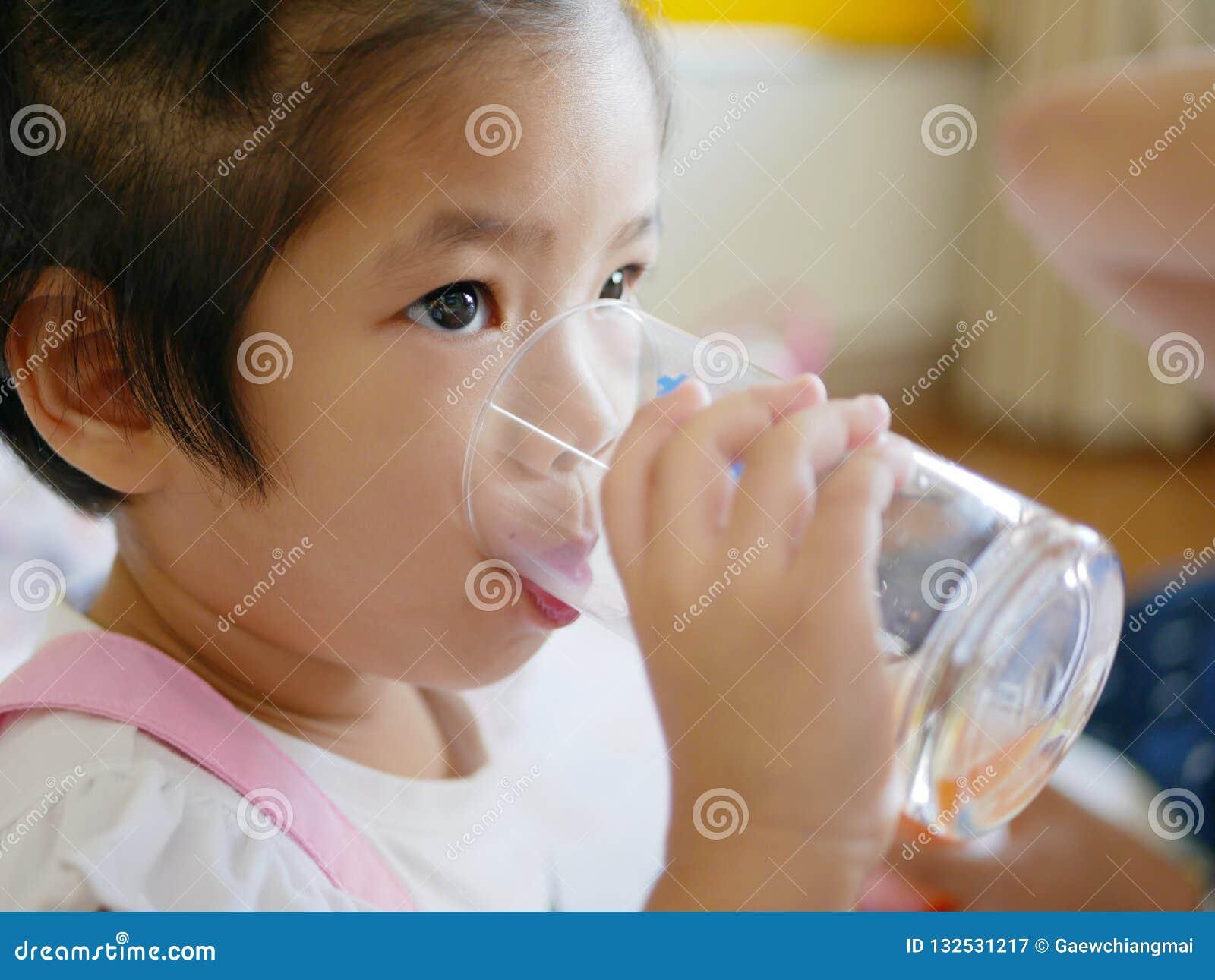 Mała Azjatycka dziewczynki woda pitna od szkła/filiżanka sama