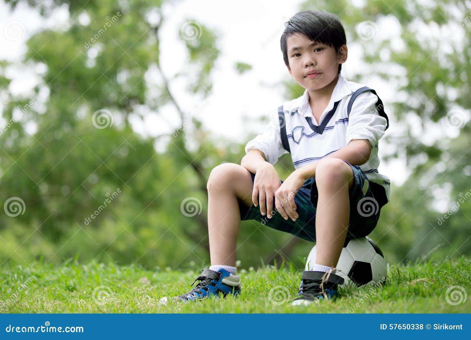 Mała azjatykcia chłopiec z futbolem przy parkiem