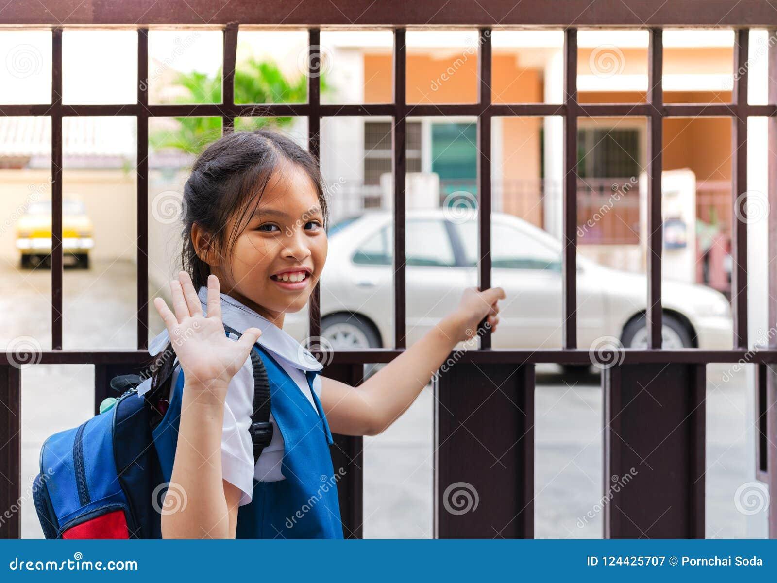 Mała azjatykcia dziewczyna w jednolitym mówi przed opuszczać szkoła w ranku z błękita plecy do widzenia - paczka