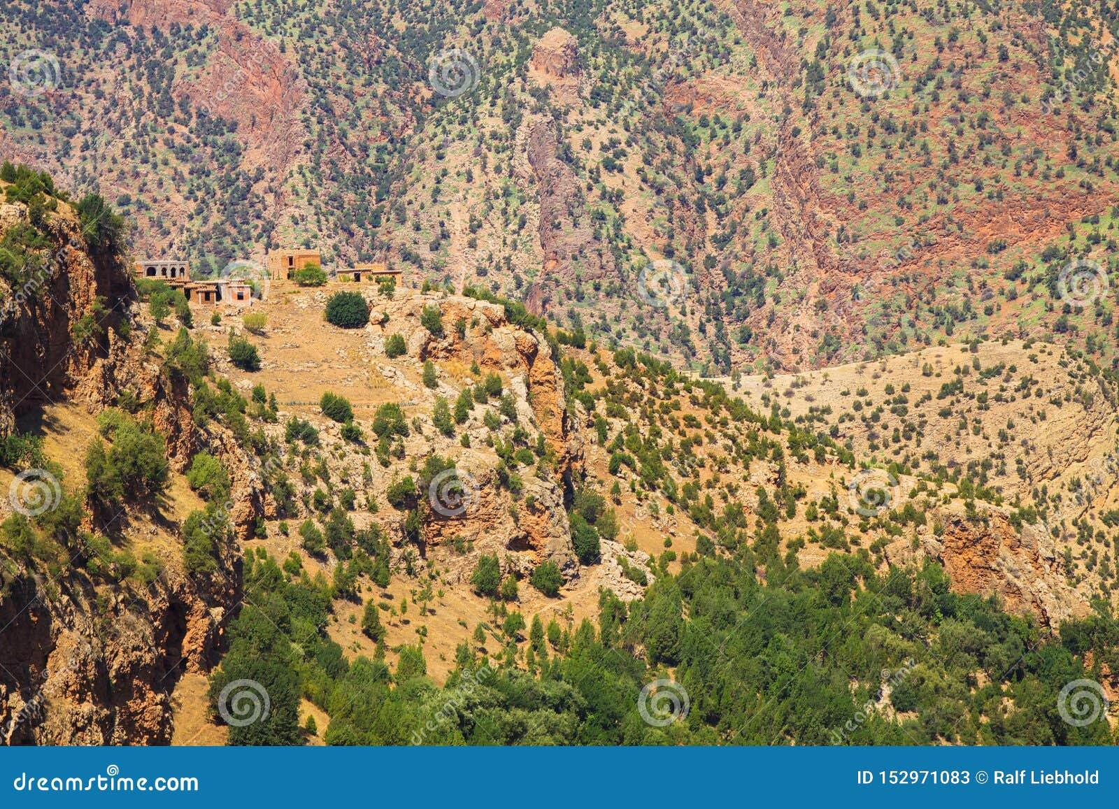 Mała berber wioska z glinianymi domami na wzgórze wierzchołku przeciw imponująco czerwonej halnej twarzy kropkującej z zielonymi