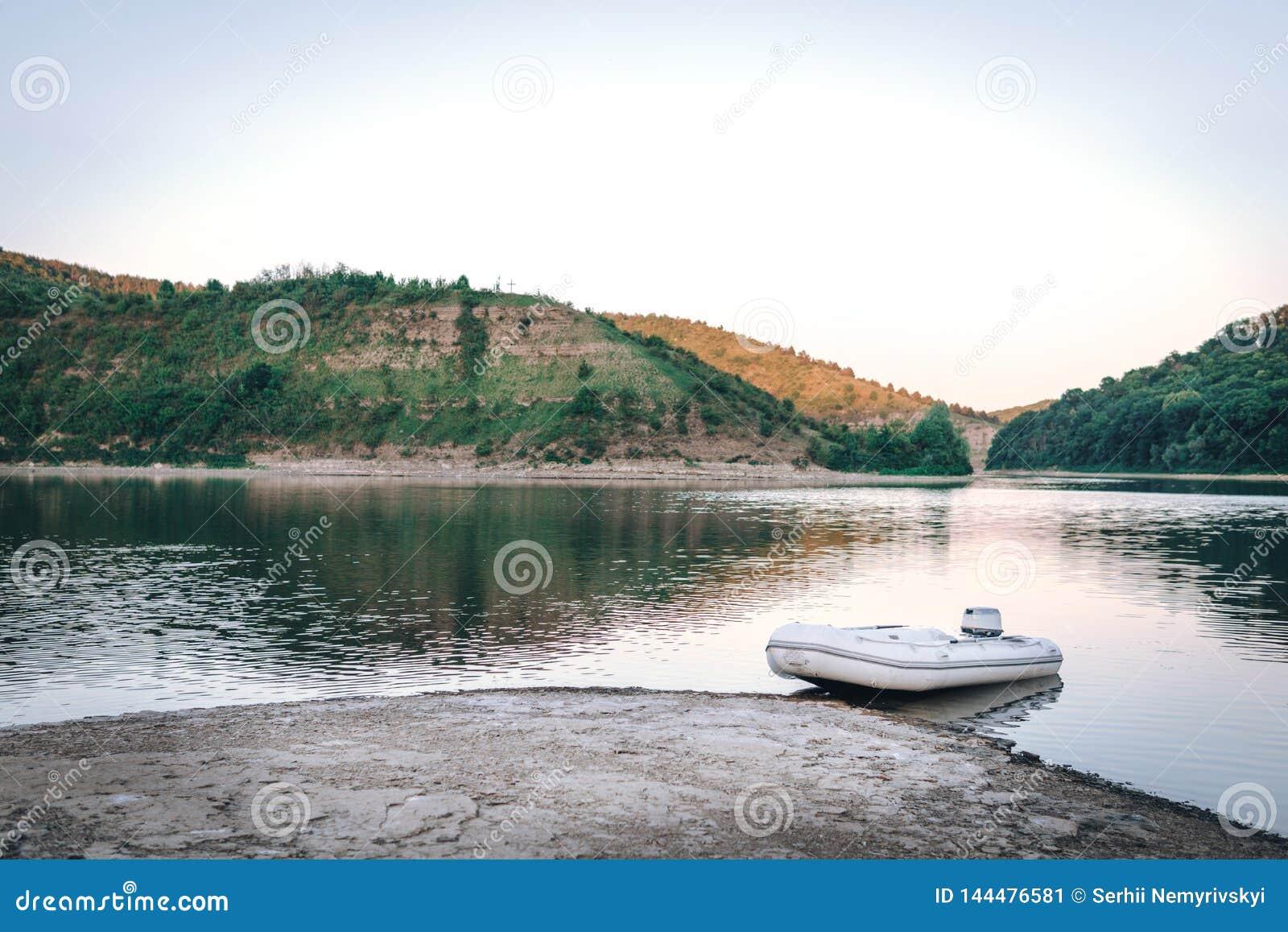 Mała biała motorowa łódź na halnej rzece, zmierzch, łowi pojęcie
