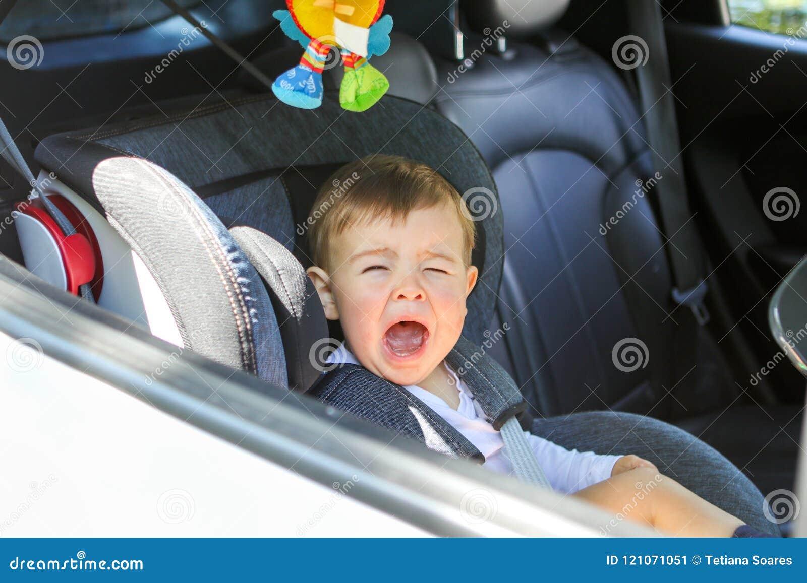 Mała chłopiec płacze w jego samochodowym siedzeniu no determinuje siedzieć w nim