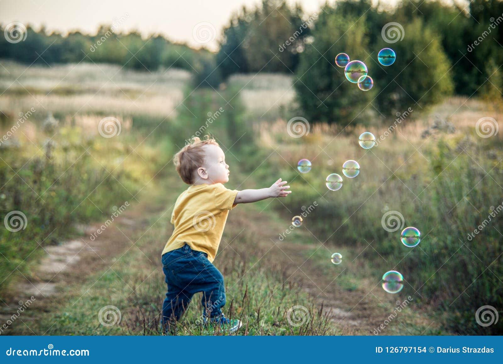Mała dzieciak chłopiec bawić się z mydlanymi bąblami