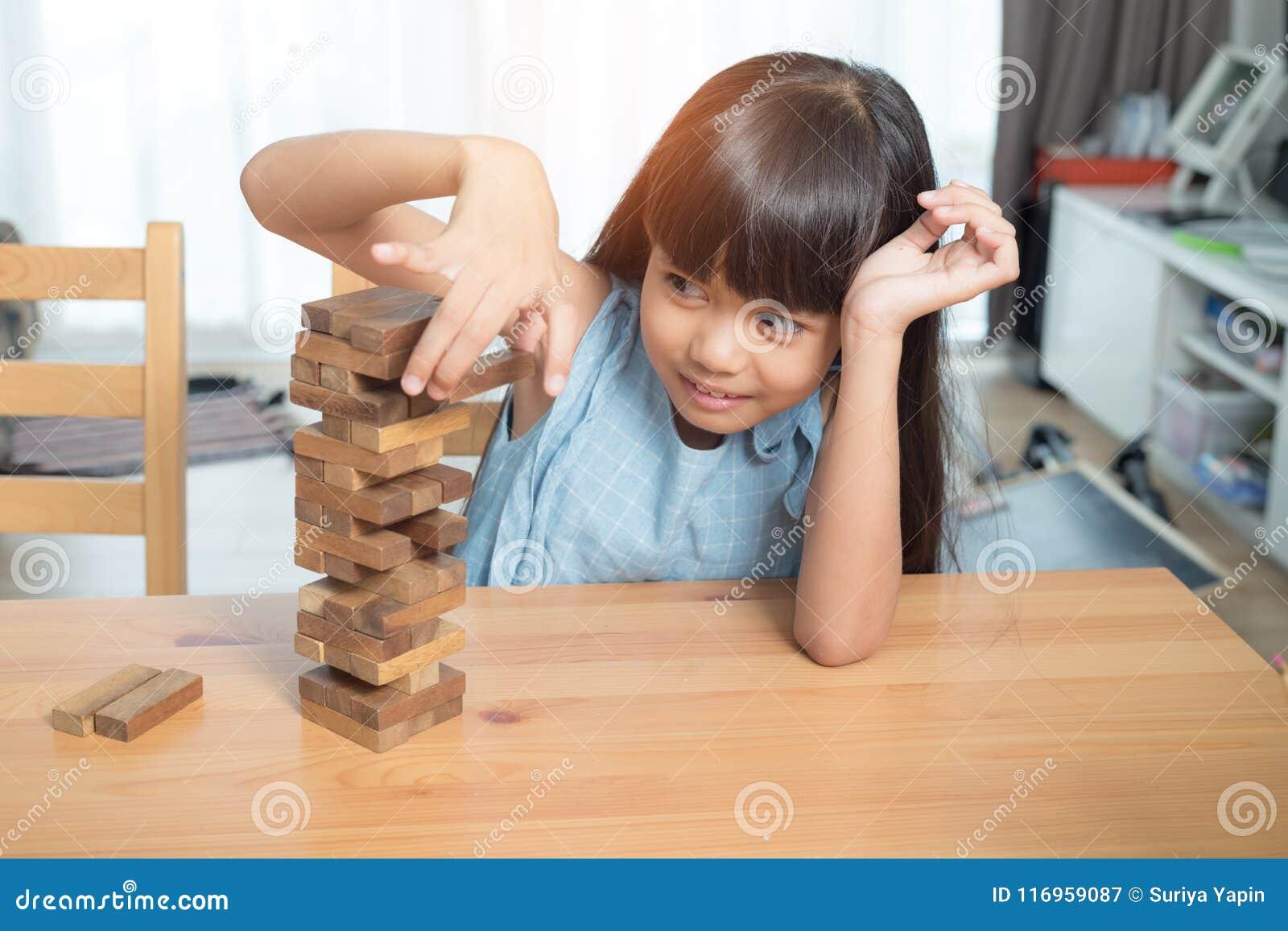 Mała dziewczynka bawić się drewnianych bloków sterty grę