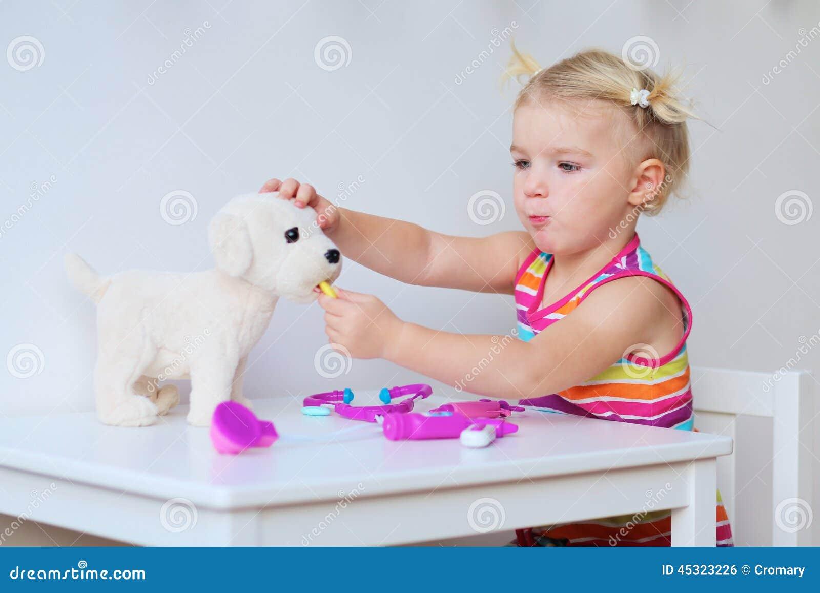 Mała dziewczynka bawić się lekarkę indoors