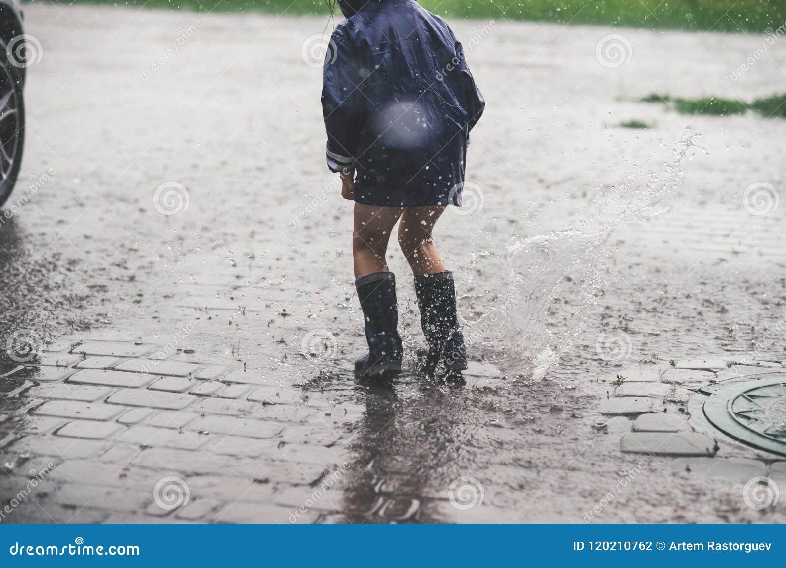 Mała dziewczynka bawić się samotnego outside w złej pogodzie