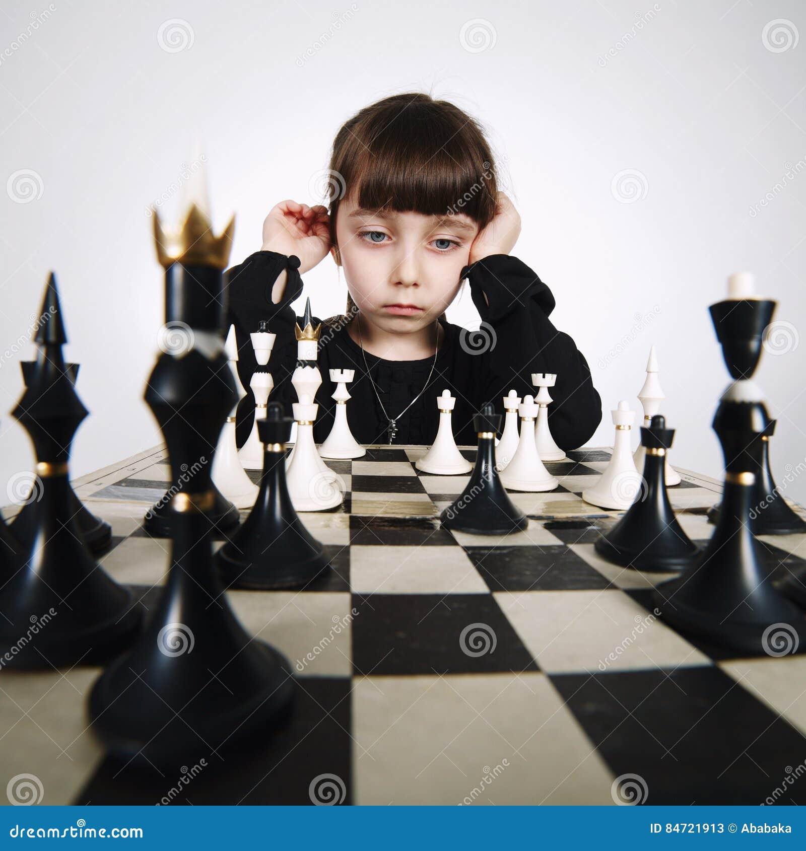 Mała dziewczynka bawić się szachy na bielu