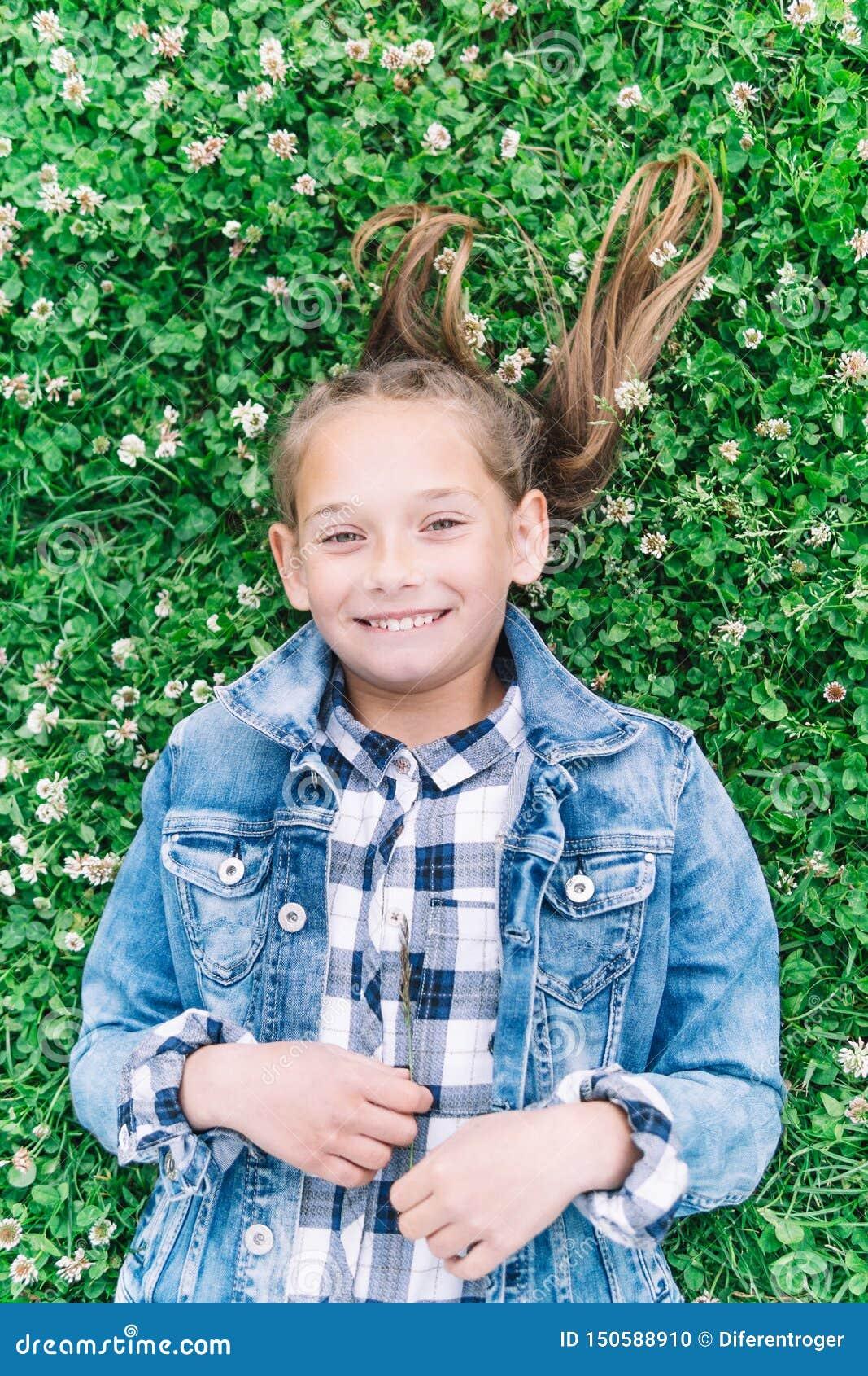 Mała dziewczynka bawić się w parku w zielonym tle z kwiatami