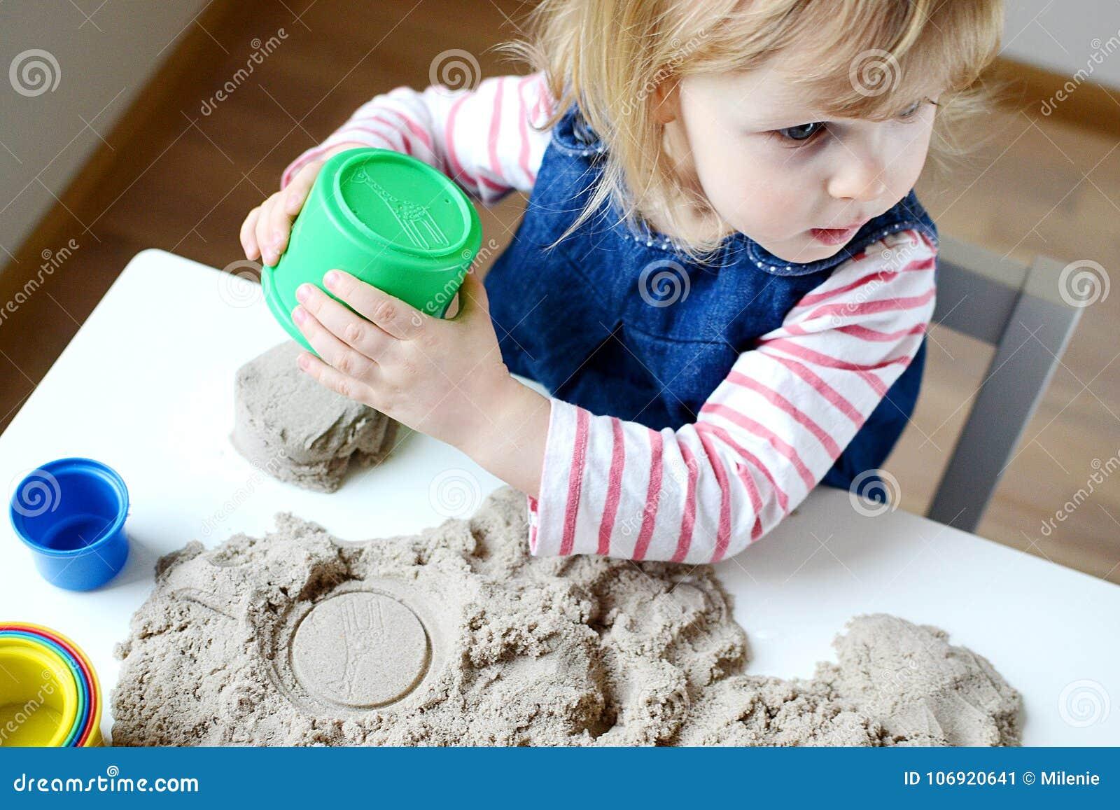 Mała dziewczynka bawić się z kinetycznym piaskiem w domu