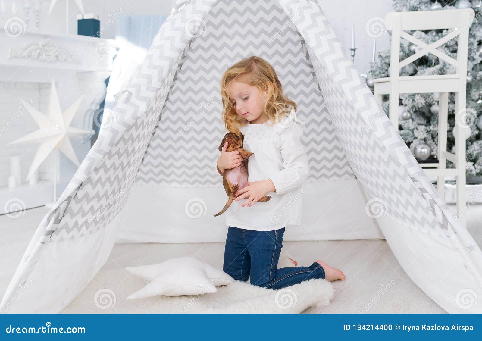 Mała dziewczynka bawić się z małym szczeniaka psem blisko wigwamu w bożego narodzenia playroom