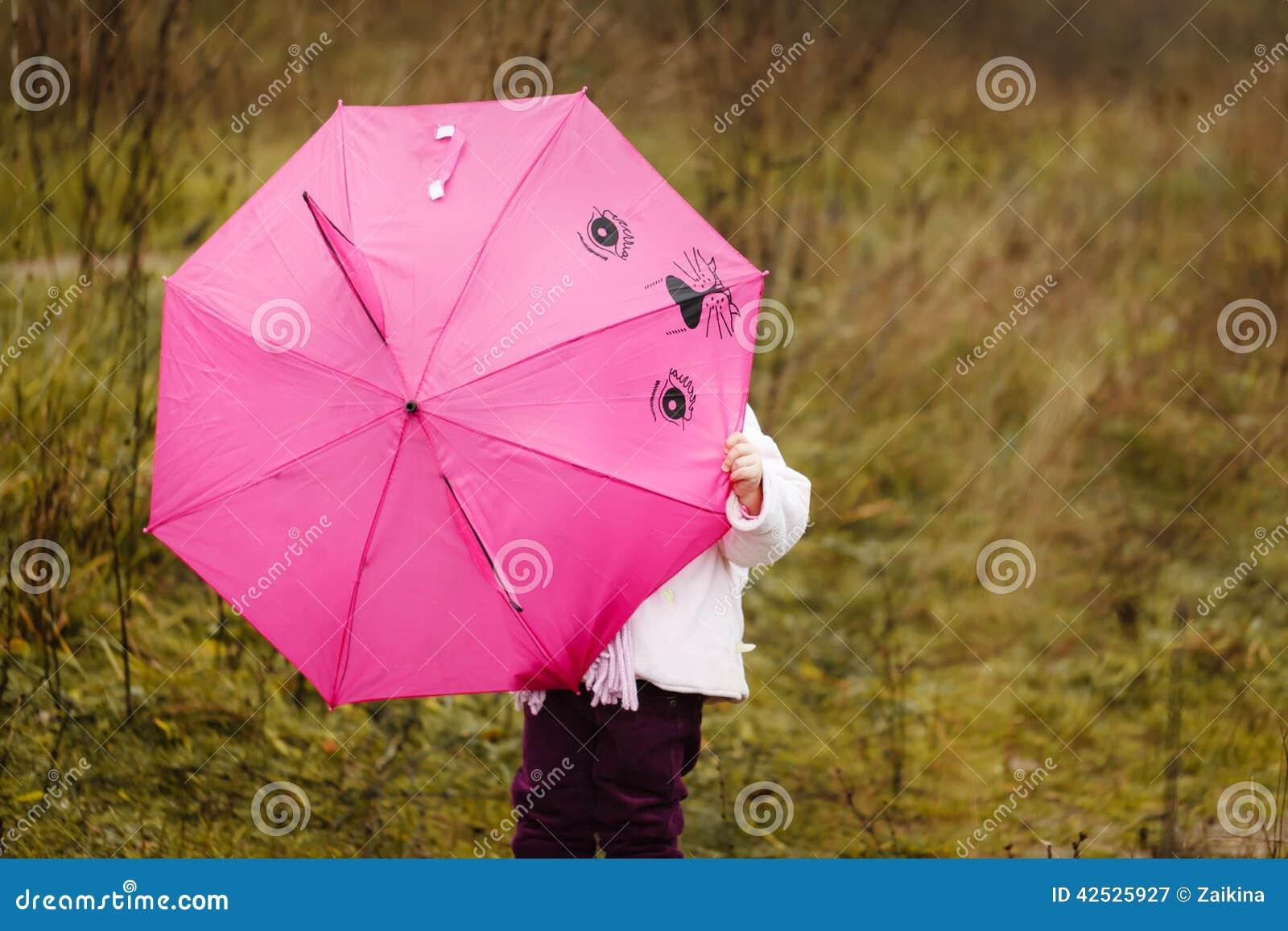 Mała dziewczynka chowałem pod różowym parasolem w jesień parku