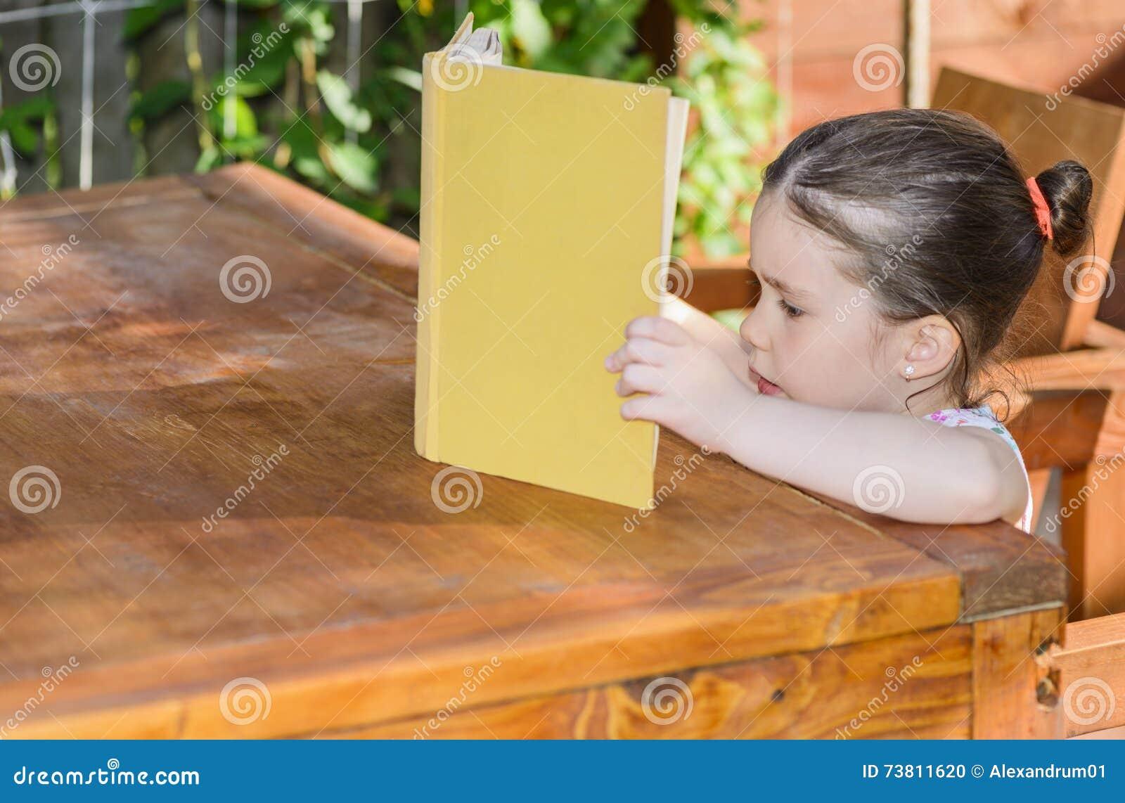 Mała dziewczynka czyta książkę plenerową