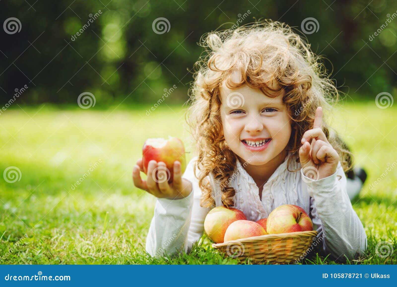 Mała dziewczynka jest jeść jabłczany i ono uśmiecha się pokazywać białych zęby