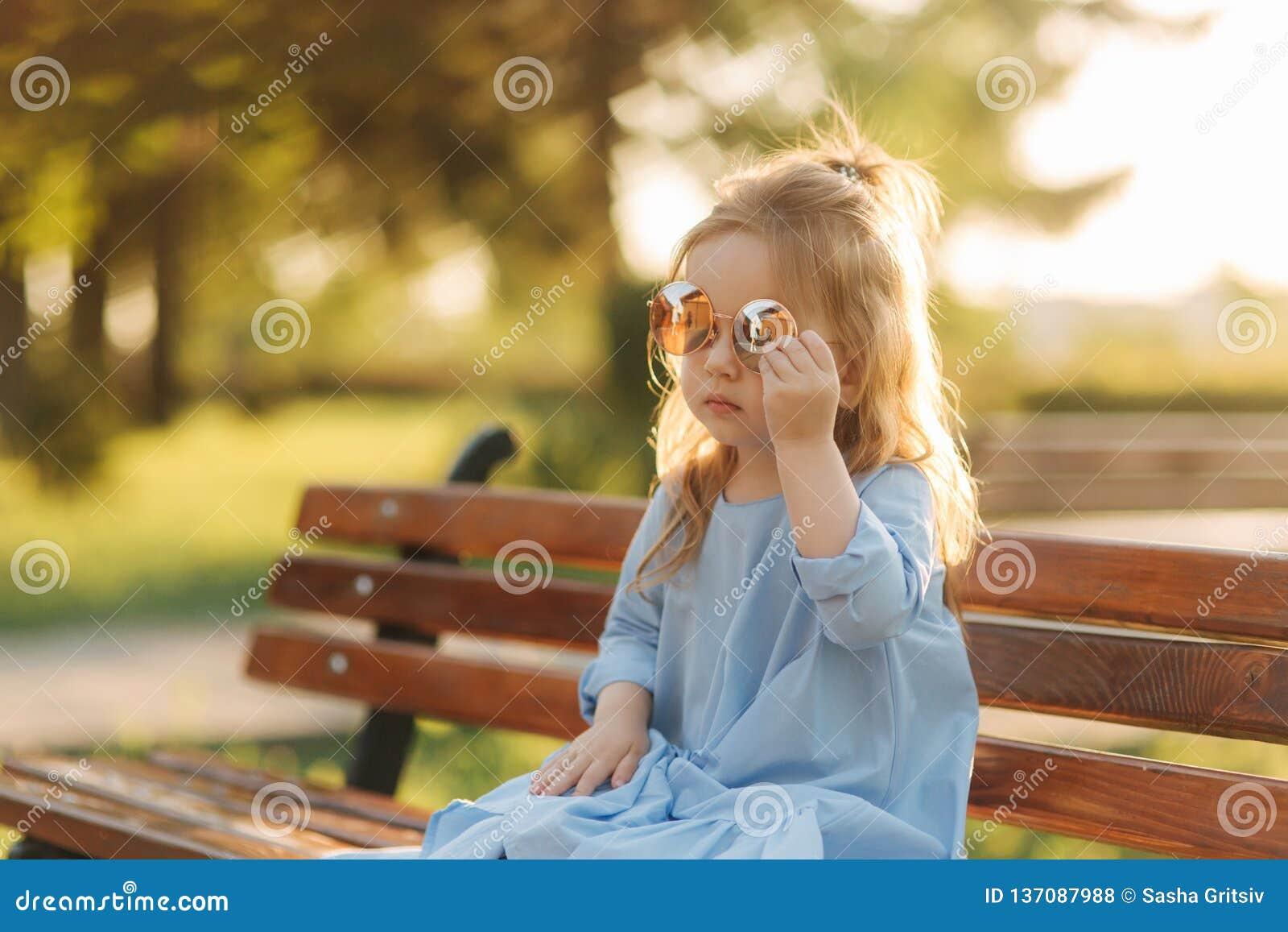Mała dziewczynka model w błękita słońca i sukni szkłach siedzi na ławce w parku
