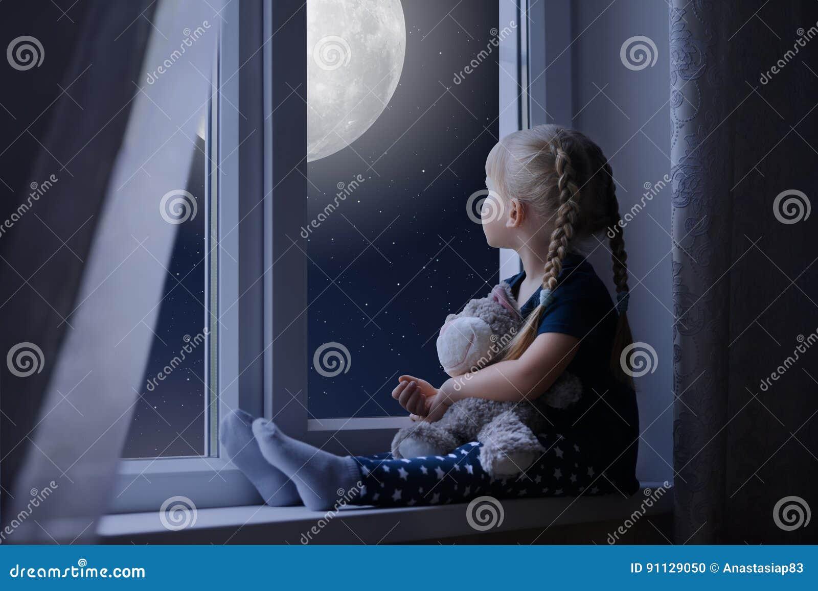 Mała dziewczynka patrzeje gwiaździstą księżyc i niebo