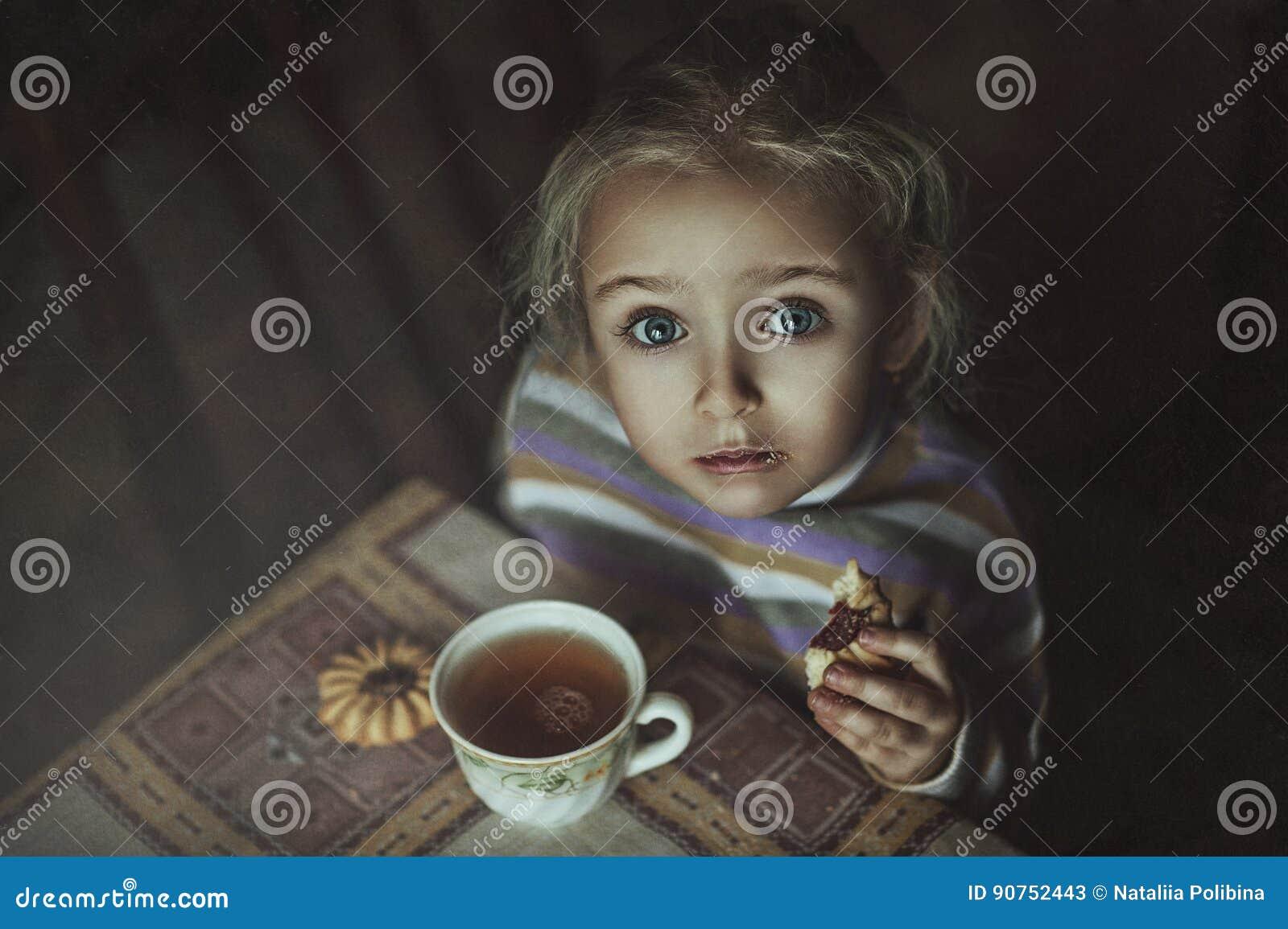 Mała dziewczynka pije herbaty z ciastkami