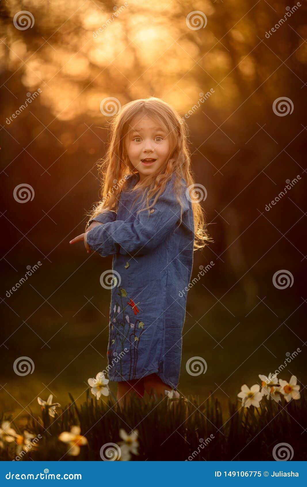 Ma?a dziewczynka plenerowy portret blisko narcyza kwitnie przy zmierzchem