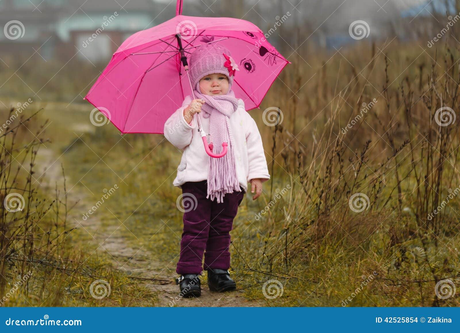 Mała dziewczynka pod różowym parasolem w spadku