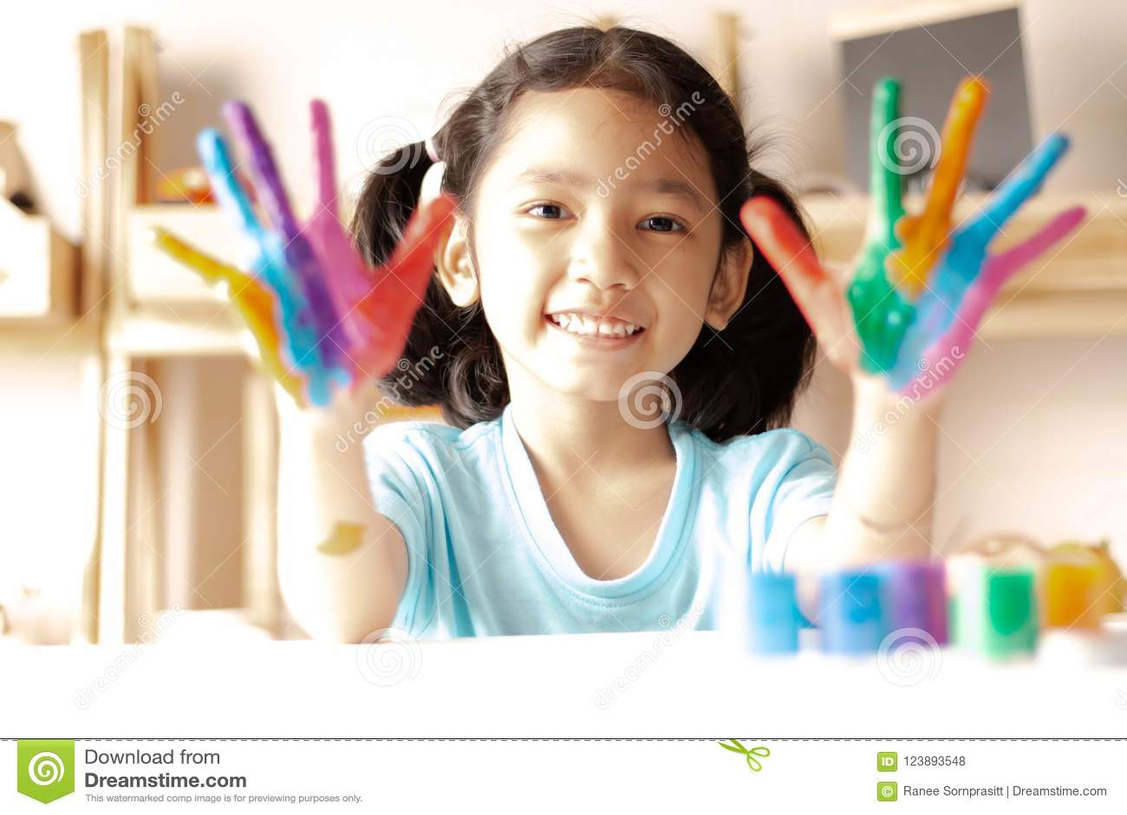 Mała dziewczynka pokazuje kolor malującego na rękach