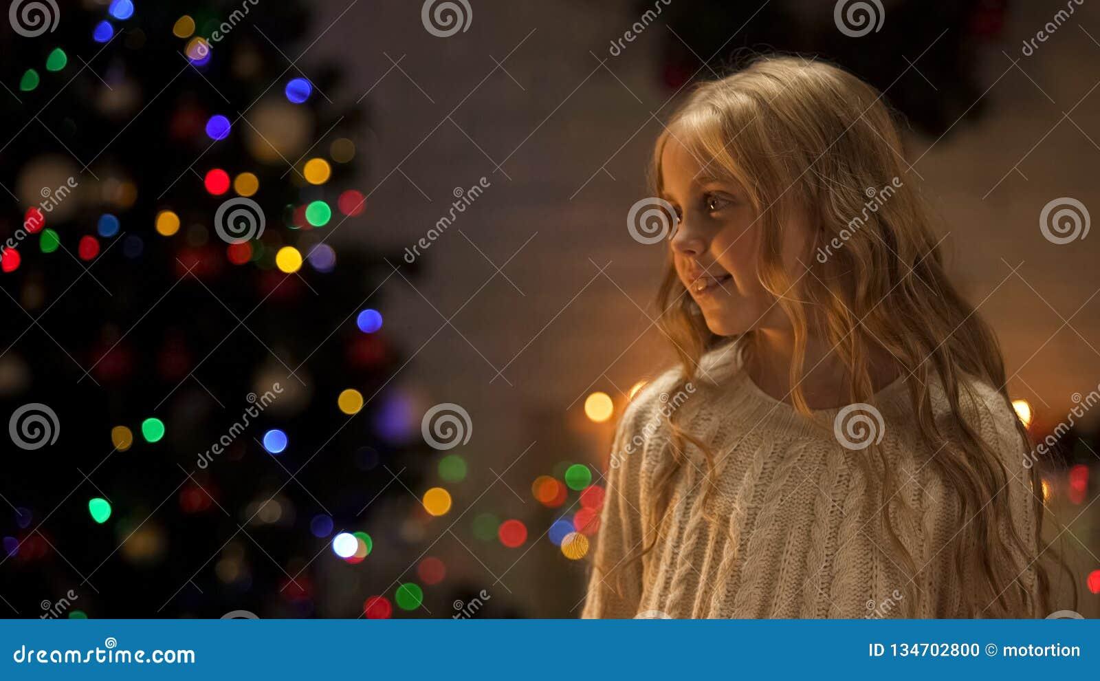 Mała dziewczynka przyglądająca za Santa blisko rozjarzonej choinki, wakacyjna antycypacja
