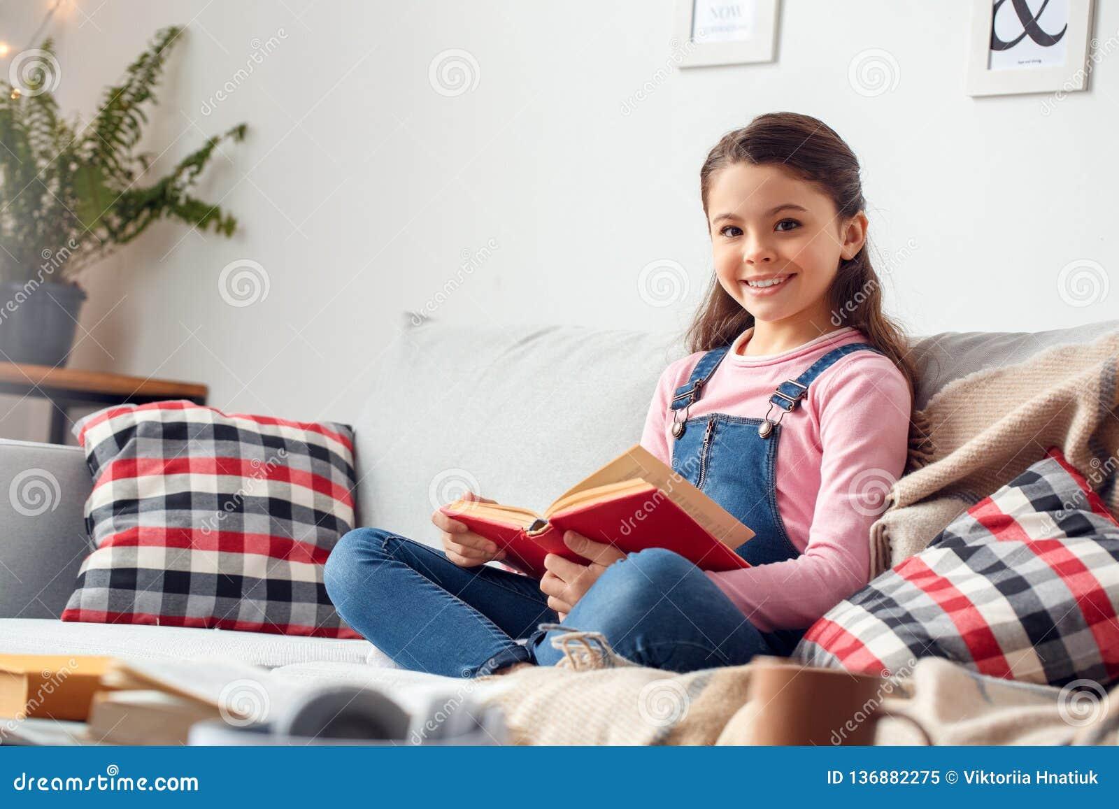 Mała dziewczynka siedzi mienie książkową przyglądającą kamerę szczęśliwą w domu