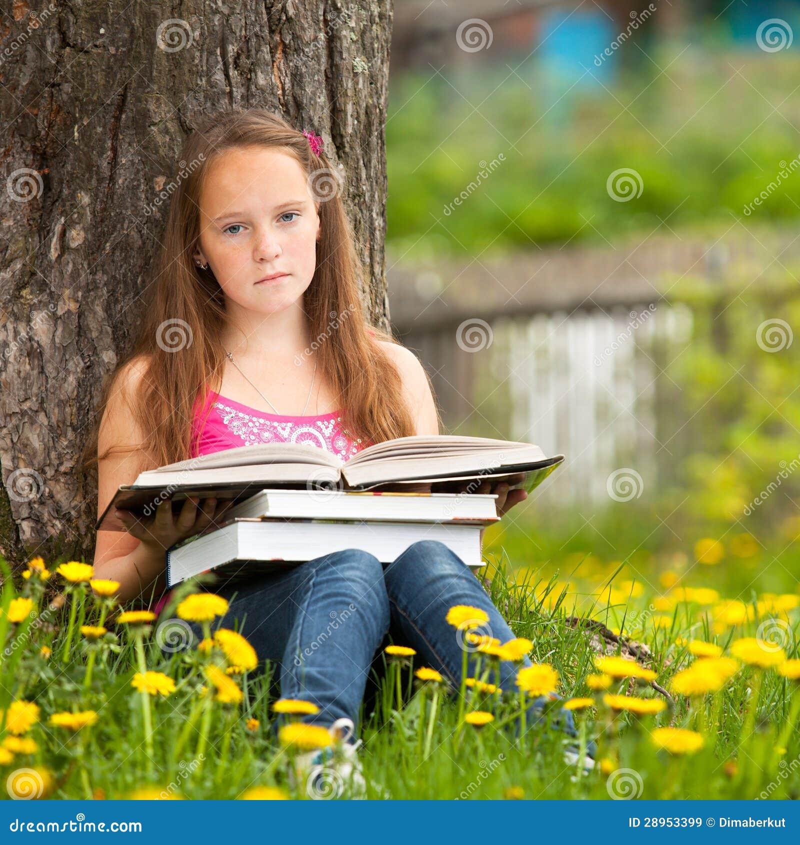 Mała dziewczynka siedzi na trawie podczas gdy czytający książkę