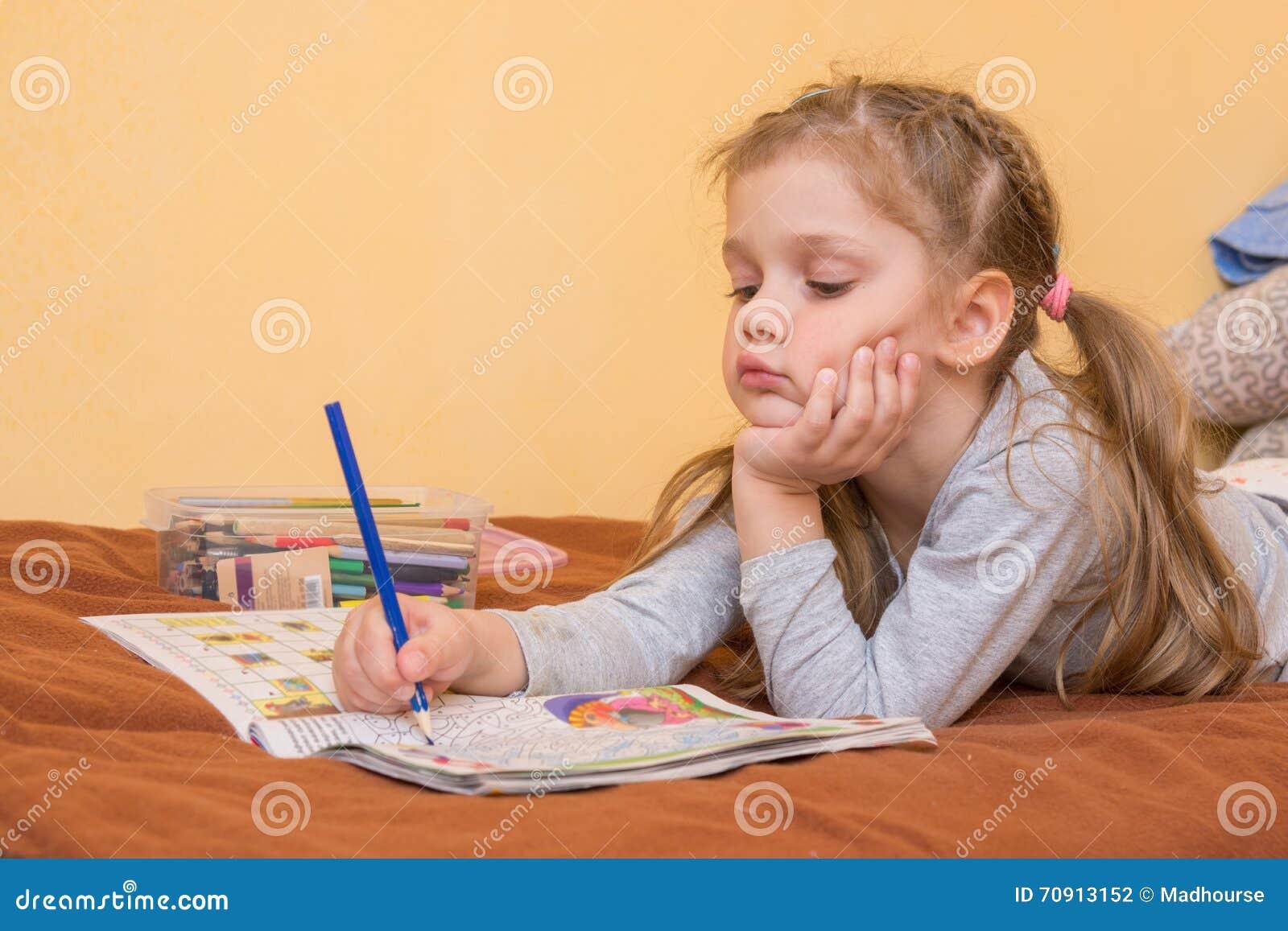 Mała dziewczynka studiuje magazyn z ołówkiem w jego ręki lying on the beach na jego żołądku i jego głowa w jego drugi ręce