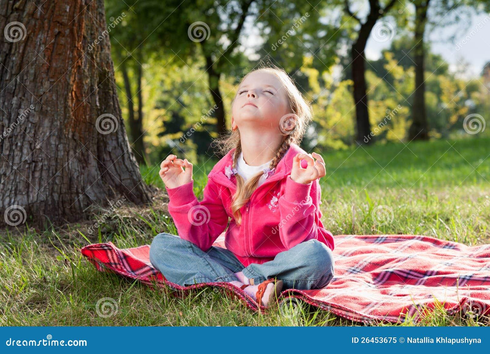 Mała dziewczynka target228_0_ w joga pozie na trawie