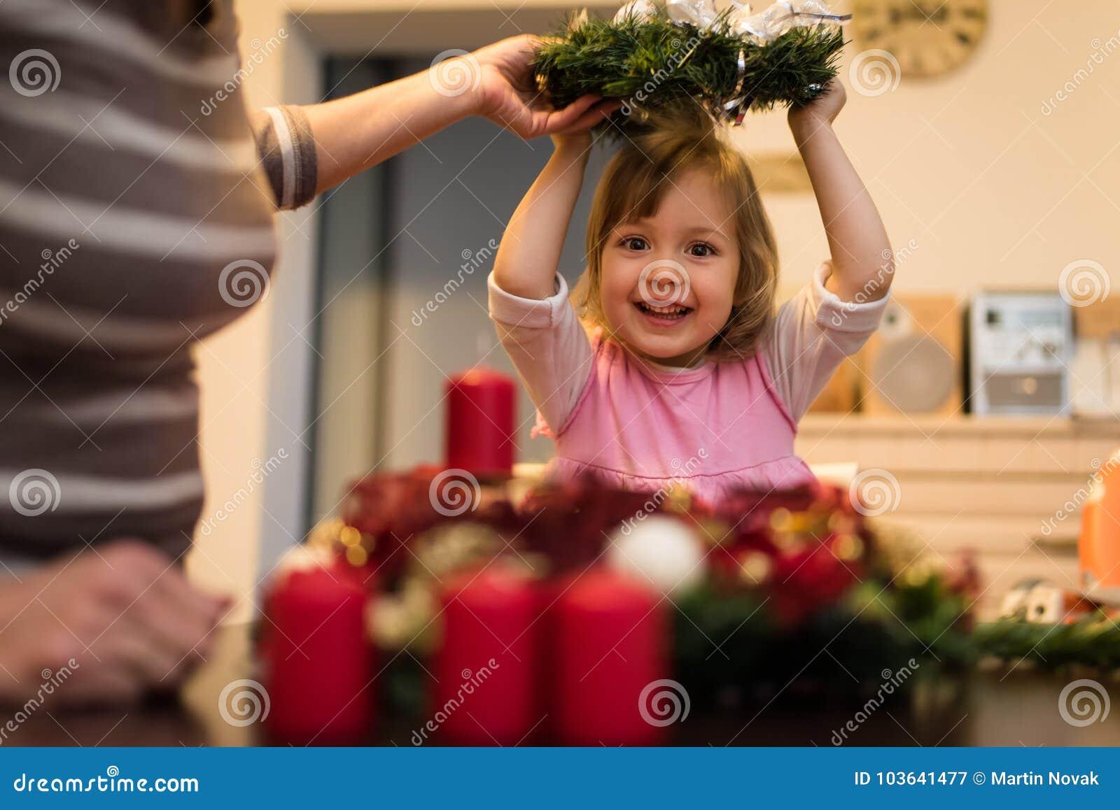 Mała dziewczynka trzyma boże narodzenie wianek nad jej głowa
