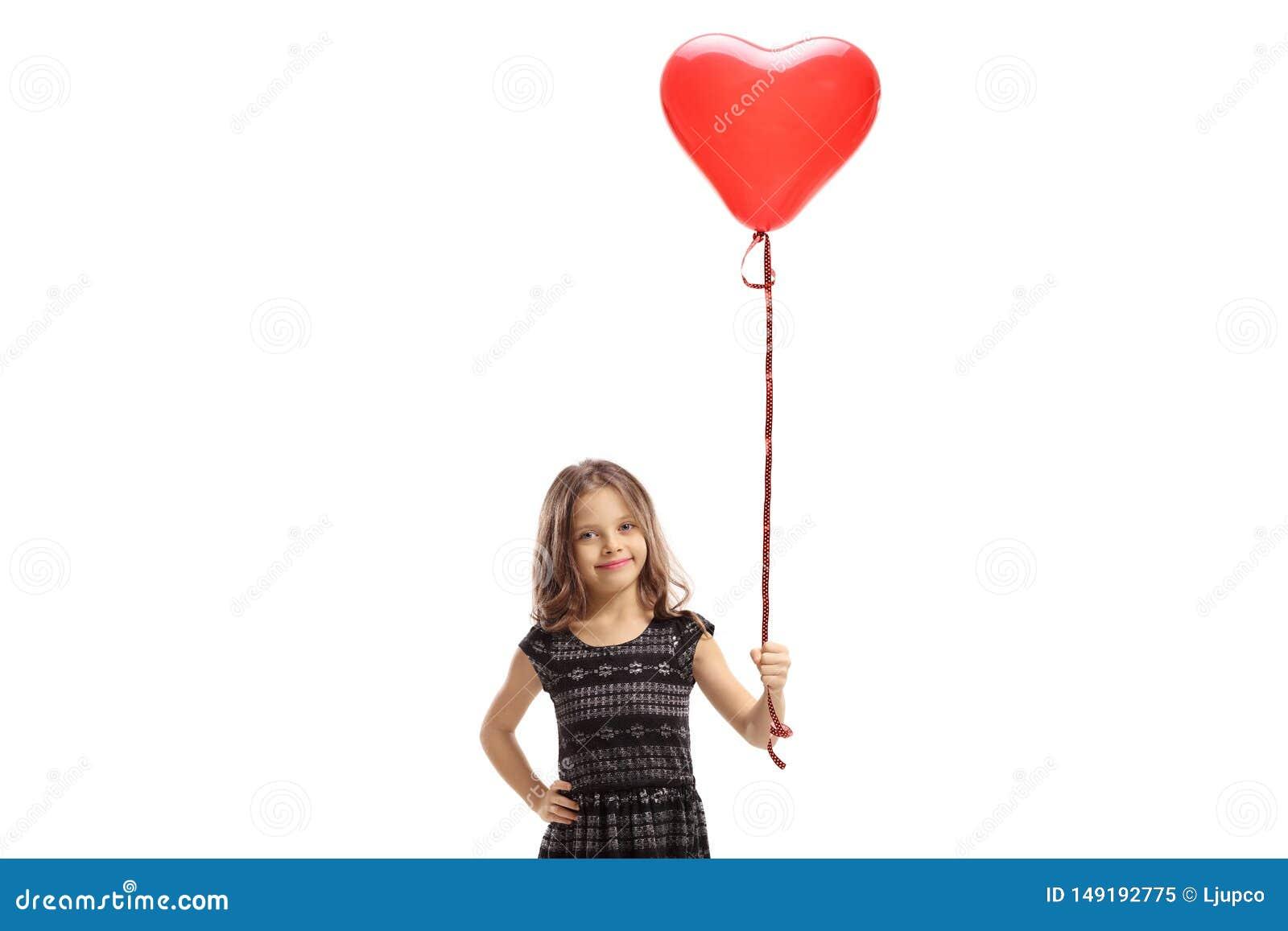 Ma?a dziewczynka trzyma czerwony serce kszta?tuj?cego balon