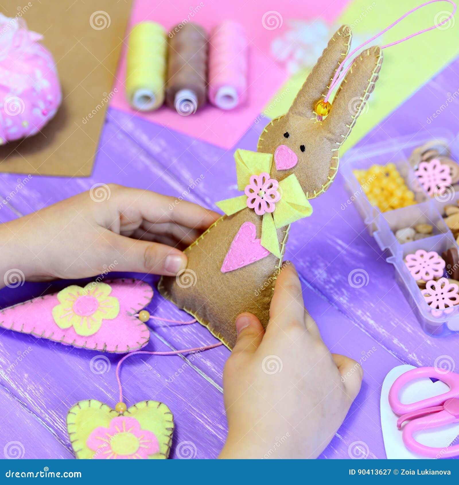 Mała dziewczynka trzyma odczuwaną Wielkanocnego królika zabawkę w rękach Dziewczyna pokazuje odczuwanego królika z sercami Handma