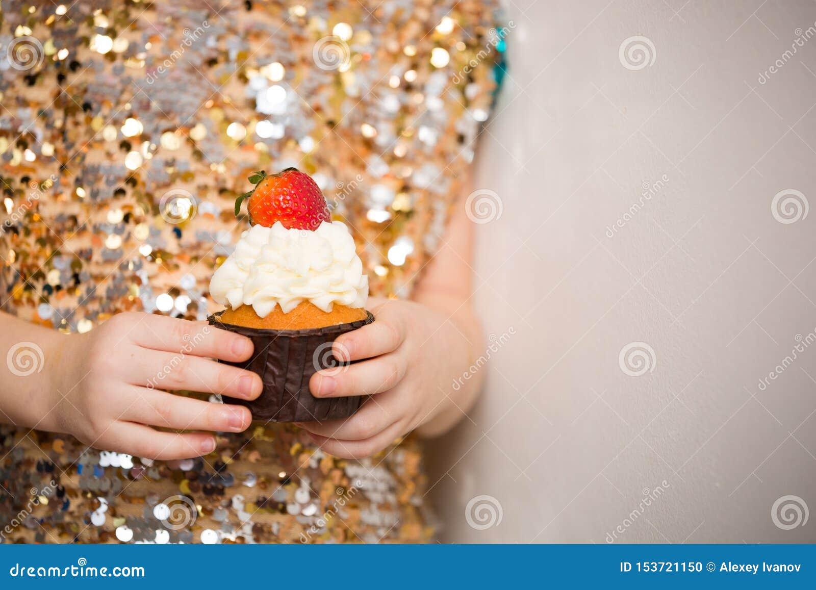 Mała dziewczynka trzyma piękną babeczkę w błyszczenie sukni, zakończenie w górę Piekarnia, s?odki jedzenie i ludzie poj??,